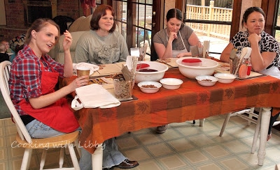 Group of women sitting at a table learning how to make Candied Yams-Sweet Potatoes.